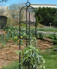 A Tidy Garden With A Black Obelisk Coming Out Of The Ground. The Steel Tubes Curve At The Top And A Green Plant At The Base Has Started To Grown Up The Side Of The Obelisk.